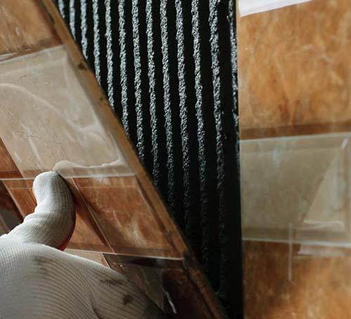 Dán từng viên gạch ốp nhà vệ sinh lên bề mặt tường phủ keo